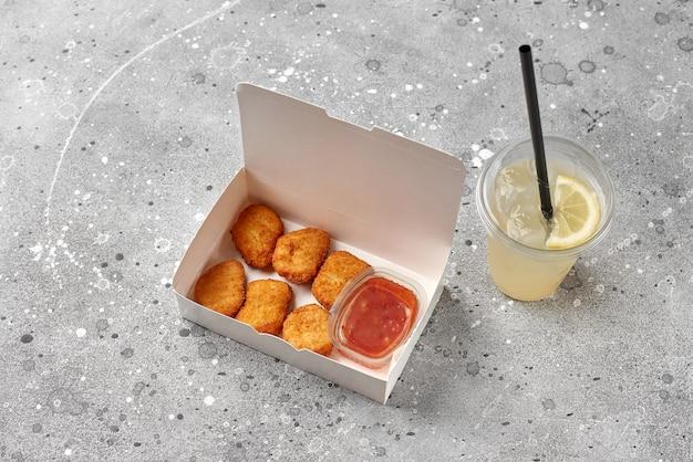 Доставка еды, еда на вынос в бумажных контейнерах с горячими куриными наггетсами и прохладительный напиток лимонад в пластиковом стакане. меню и макет логотипа