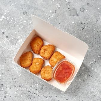 Доставка еды, еда на вынос в бумажных контейнерах с горячими куриными наггетсами. меню и макет логотипа. вид сверху.