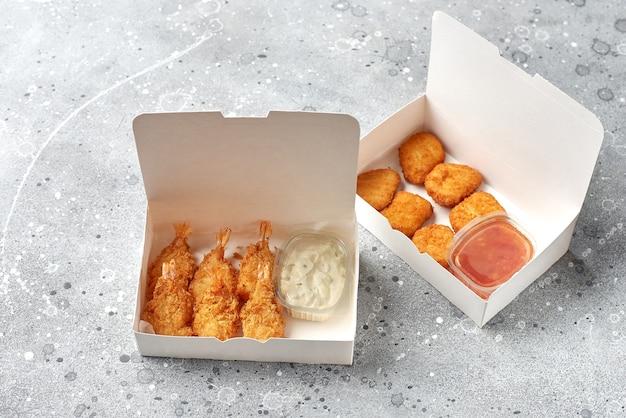 Доставка еды, еда на вынос с жареными креветками в кляре и горячими куриными наггетсами. бумажные контейнеры, меню и макет логотипа