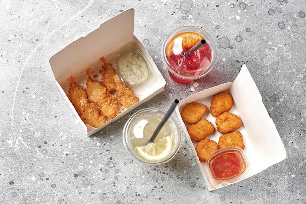 Доставка еды, еда на вынос с жареными креветками в кляре, горячие куриные наггетсы и напитки с лимоном. бумажные контейнеры. вид сверху. меню