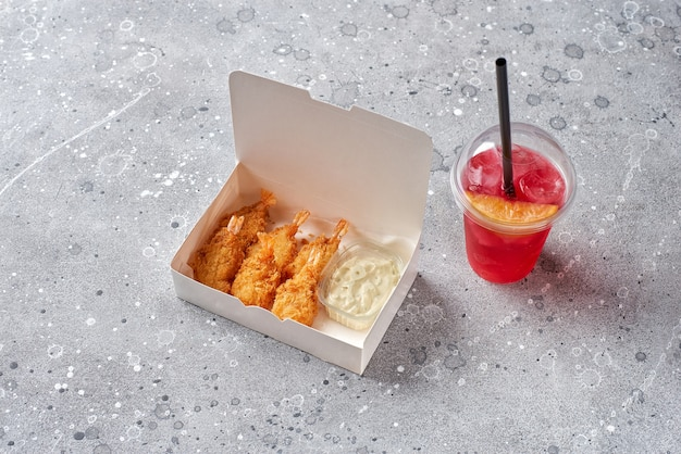 Food delivery, takeaway food with tempura shrimps and refreshment drink lemonade in plastic glass, paper containers with shrimps and sauce. menu and logo mockup