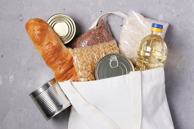 Food delivery. textile shopping bag with food supplies on gray concrete surface. rice, buckwheat, pasta, bread, canned food, vegetable oil.