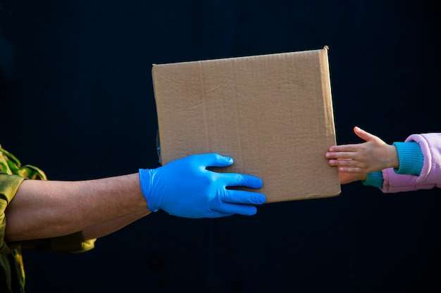 あなたの家への食品配達。年金受給者、貧困層、人口への支援。ゴム手袋の宅配便が子供に食べ物の箱を与えます。手から手へ