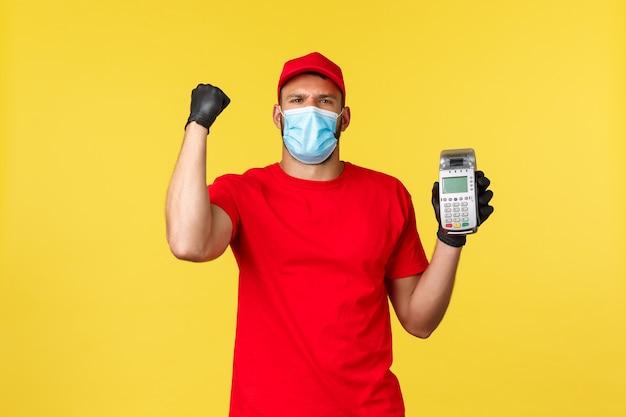 食品の配達、追跡、covid-19および自己検疫の概念。赤いユニフォーム、医療用マスク、手袋を着用した陽気で興奮した宅配便、「はい」と叫び、非接触型決済用のpos端末を表示
