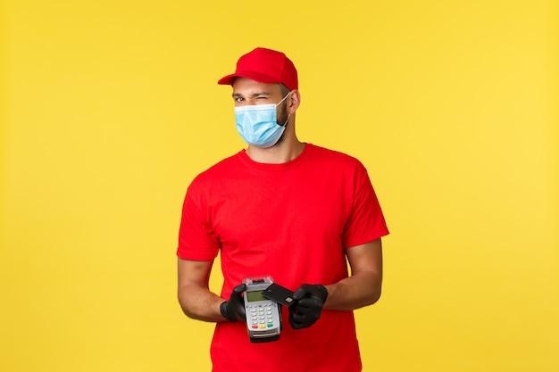 食品の配達、追跡、covid-19および自己検疫の概念。赤いユニフォームを着たフレンドリーな宅配便、医療用マスクと手袋、カメラでウィンク、決済端末とクレジットカードで非接触型決済を要求