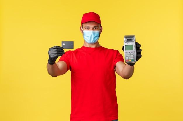 食品の配達、注文の追跡、covid-19および自己検疫の概念。医療用マスクと手袋を着用した陽気な若い宅配便業者は、pos端末とクレジットカードで非接触型決済を提案します