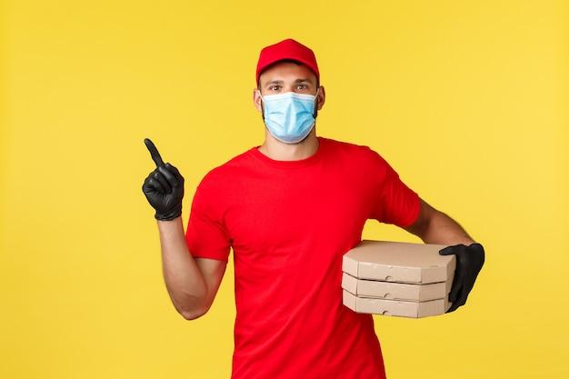 Доставка еды, отслеживание заказов, covid-19 и концепция самокарантина. курьер в красной форме и медицинской маске, обеспечивает быструю бесконтактную доставку, указывая пальцем влево, держит пиццу