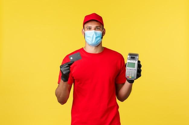 食品の配達、注文の追跡、covid-19および自己検疫の概念。赤いユニフォームを着た宅配便、医療用マスクと手袋、pos端末とクレジットカードを表示、コロナウイルス中の非接触型決済