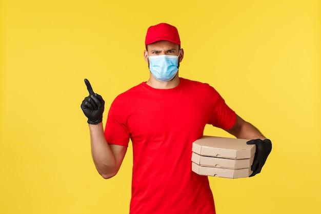 Доставка еды, отслеживание заказов, covid-19 и концепция самокарантина. недовольный серьезный курьер в красной форме, медицинской маске и перчатках, озабоченно хмурясь, указывая влево, держа заказ на пиццу