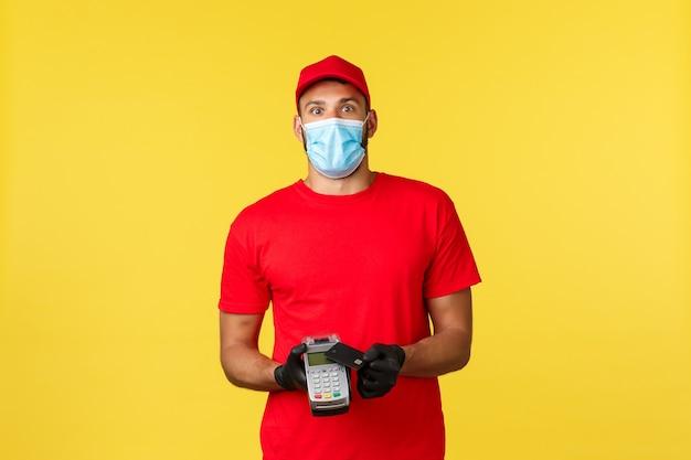 食品の配達、注文の追跡、covid-19および自己検疫の概念。赤いユニフォーム、医療用マスクと手袋、カメラを見つめる、pos端末とクレジットカードを使用した興奮して面白がっている宅配便