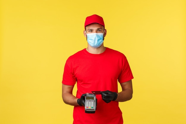 食品の配達、注文の追跡、covid-19および自己検疫の概念。赤いユニフォーム、医療用マスク、手袋を着用したフレンドリーな宅配便。pos端末のクレジットカードを使用して非接触型決済を行います。