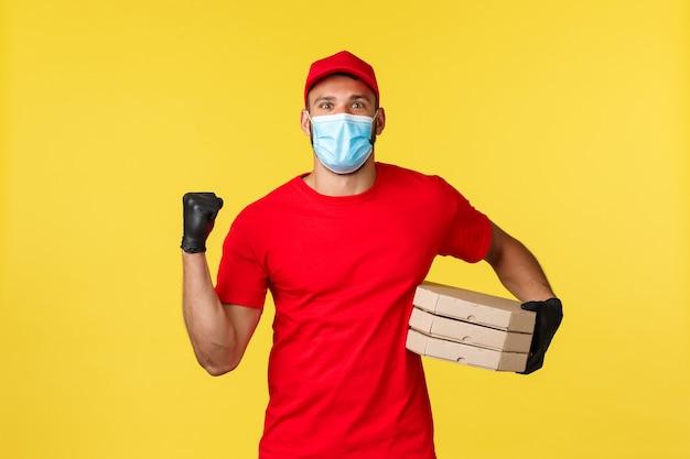 Доставка еды, отслеживание заказов, covid-19 и концепция самокарантина. радующийся улыбающийся курьер в медицинской маске и красной униформе, держащий пиццу, наводящий порядок, качающий кулаком от радости, успеха или достижения