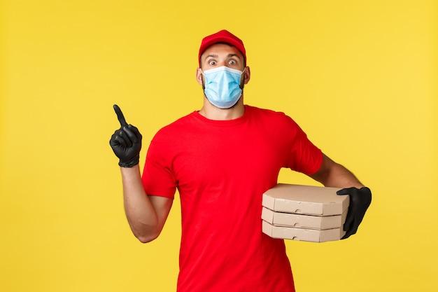 Доставка еды, отслеживание заказов, covid-19 и концепция самокарантина. шокированный молодой курьер в красной форме и медицинской маске, указывая пальцем в верхнем левом углу, доставляет пиццу в дом клиентов