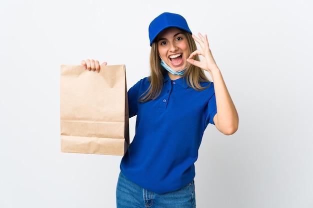 食品配達の女性と指でokの標識を示す分離された白のマスクでコロナウイルスから保護