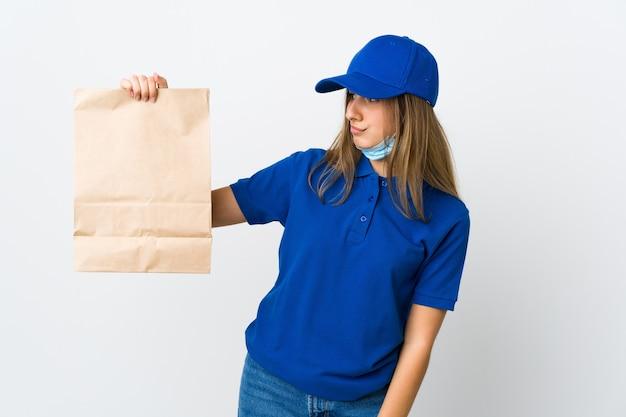 Женщина-доставщик еды и защита от коронавируса с маской над изолированной белой стеной с грустным выражением лица
