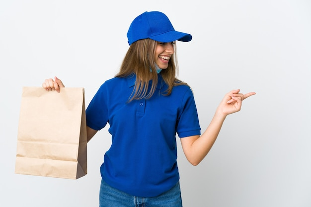 Food delivery woman and protecting from the coronavirus with a mask over isolated white wall pointing to the side to present a product