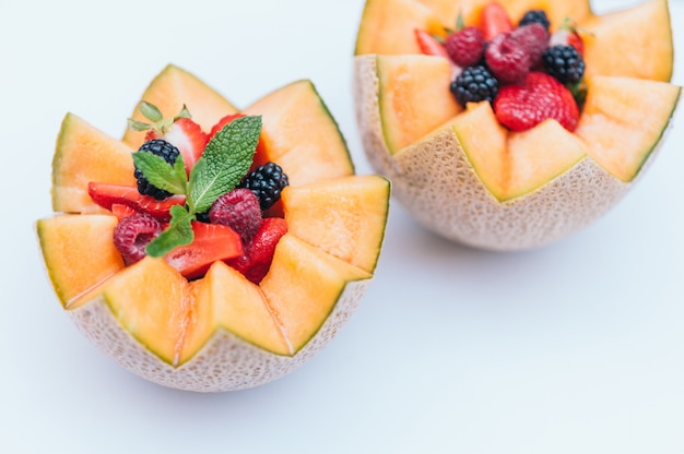 Food design and healthy nutrition concept. delisious fresh raspberry, strawberry and blackberry with mint in carved melon. cantaloupe with fruit against white background.