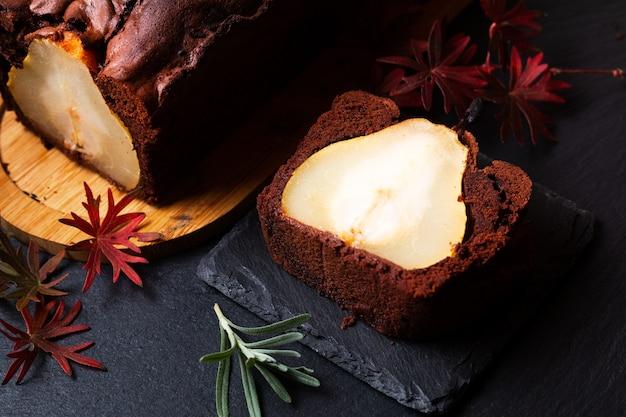 フードデザートのコンセプト自家製の素朴なチョコレートケーキまたはブラウニーと洋ナシのケーキ、コピースペース付きの黒いスレート石のボード