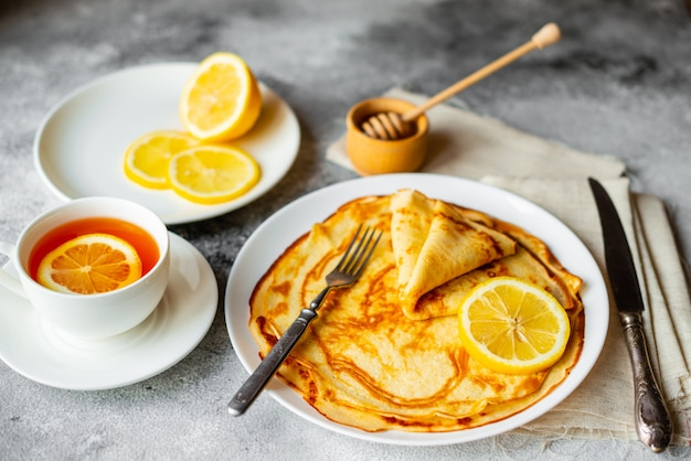 Food, dessert, pastries, pancake, pie. tasty beautiful pancakes with banana and honey on a concrete background