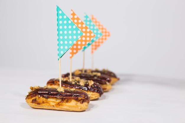 Концепция еды, десертов и выпечки - эклеры с шоколадом, оформленные в виде корабля