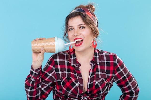 음식, 다이어트, 재미있는 개념 - 파란 배경 위에 커피나 칵테일을 마시는 핀업 여성.