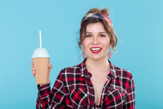 食べ物、ダイエット、楽しいコンセプト-青い表面にコーヒーやカクテルを持っているピンナップ女性