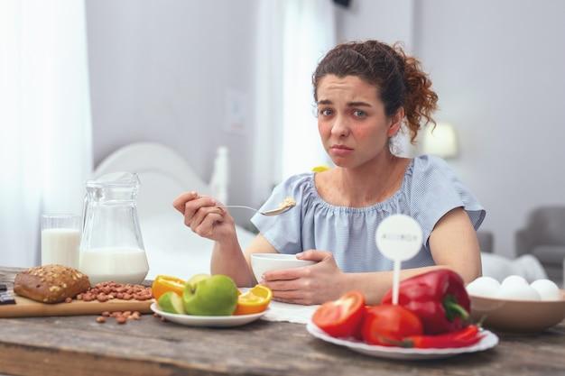 食べ物の不満。胃のむかつきに苦しんで健康的な栄養価の高い食事を楽しんでいない体調不良の思春期の女性