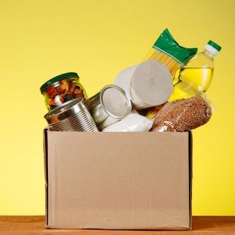 食糧寄付の概念。黄色の背景に寄付のための食糧と募金箱。コロナウイルスのパンデミックに関連した高齢者への支援。正方形の画像