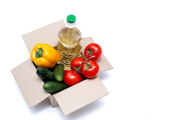 食糧寄付の概念白い背景の上の寄付のための食糧が付いている募金箱白で隔離される製品が付いている人々の箱を助けなさい