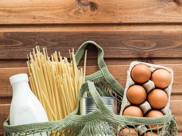 파스타, 통조림 식품 캔, 우유 병, 나무 배경에 계란 식품 기부 면화 메쉬 가방. 평면도, 평면 위치, 복사 공간.