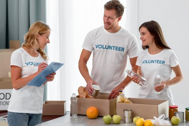 음식과 함께 상자를 준비하는 음식 기부 자원 봉사자