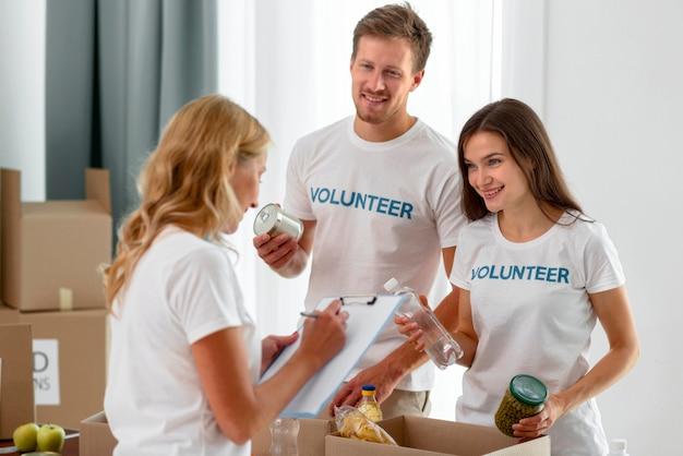 Волонтеры пожертвования еды готовят коробки