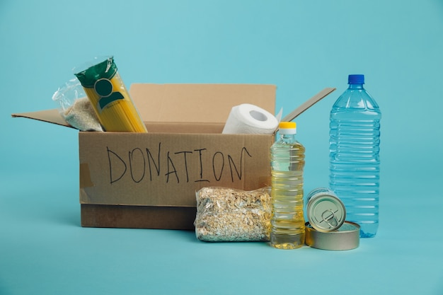食糧寄付の概念。青い背景の段ボール箱にさまざまな缶詰食品、パスタ、シリアル