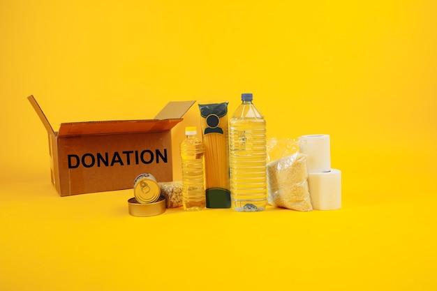 食糧寄付の概念。黄色の背景の段ボール箱にさまざまな缶詰、パスタ、シリアル。
