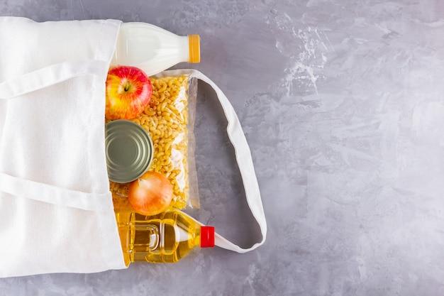 Продовольственные пожертвования в льняной сумке. эко-сумка с едой. вид сверху. копировать пространство