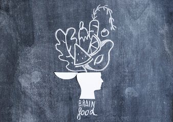 Food drawn over the open head paper cutout with text on chalkboard
