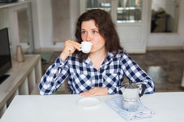 食べ物、飲み物、人々の概念。コーヒーハウスの美しい若い女性はコーヒーを飲みます。