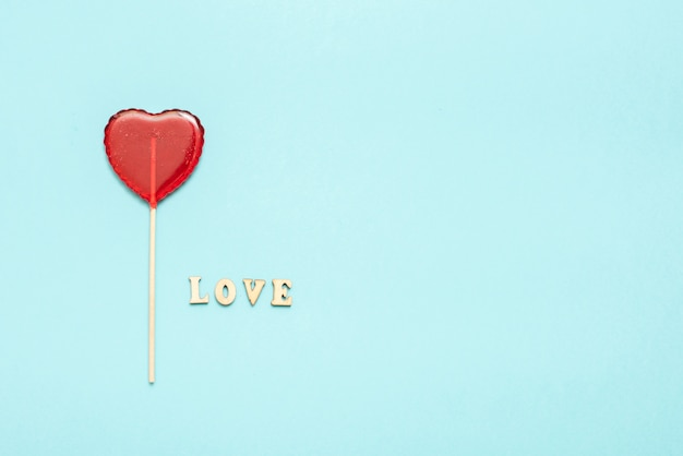 Food and drink, holidays concept. heart shaped lollipop for love valentines day with blue background. copy space