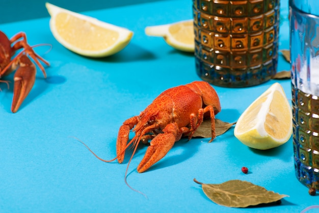 Food and drink still life scenes. sparkling beer glasses and red boiled crawfish with lemon slices and spices.