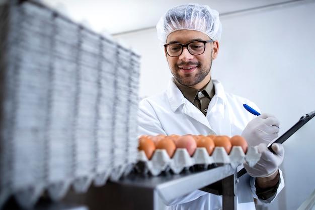 Технолог пищевой фабрики контролирует производство продуктов питания и яиц на ферме.