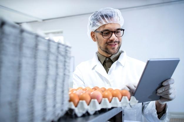 흰색 코트 헤어 넷 및 태블릿 컴퓨터의 식품 가공 공장에서 계란 생산을 제어하는 위생 장갑의 식품 공장 기술자.