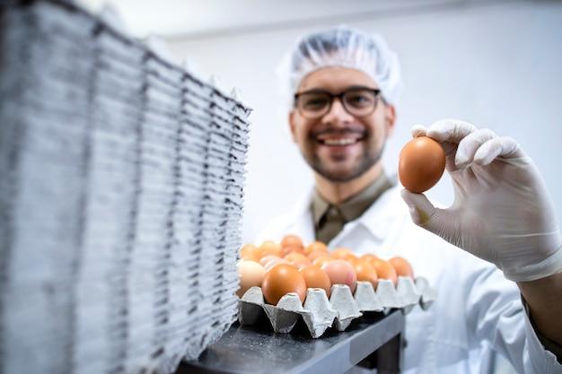 산업용 계란 포장 기계 옆에 서서 계란을 들고있는 식품 공장 기술자.