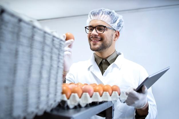 흰색 코트 헤어 네트 및 태블릿 컴퓨터의 식품 가공 공장에서 계란 품질을 확인하는 위생 장갑의 식품 공장 노동자.