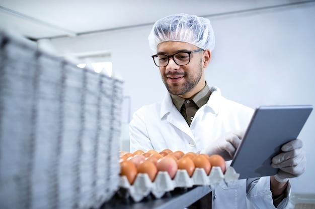 흰 코트 헤어 네트 및 태블릿 컴퓨터의 식품 가공 공장에서 계란 생산을 제어하는 위생 장갑의 식품 공장 노동자.