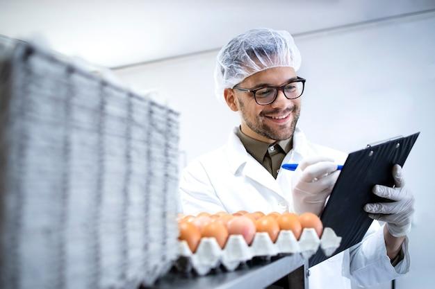 Рабочий пищевой фабрики в белом халате с сеткой для волос и гигиенических перчатках контролирует производство яиц на пищевом заводе.