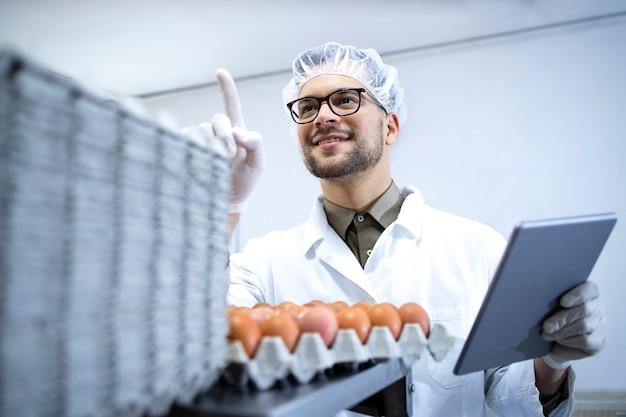 유통 및 시장 판매를위한 준비가 태블릿 컴퓨터에 계란 상자를 세는 흰색 코트 헤어 네트 및 위생 장갑에 식품 공장 노동자.