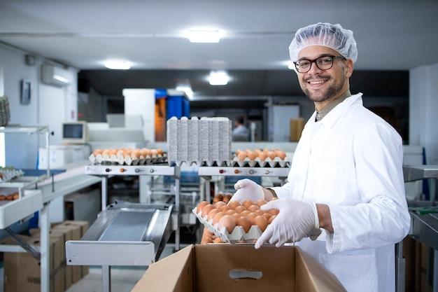 흰 코트 헤어 넷과 위생 장갑의 식품 공장 노동자는 골판지 상자에 계란을 포장하여 시장을 준비합니다.