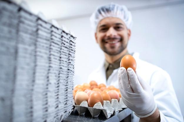 산업용 계란 포장 기계에 의해 서서 계란을 들고 식품 공장 노동자.