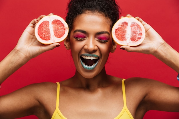 Food fashion delighted afro american woman having fun holding two halves of fresh ripe grapefruit at face, isolated over red wall