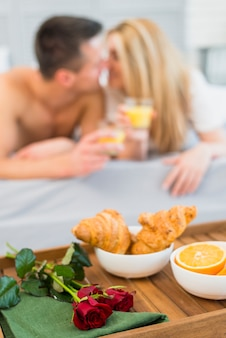 Food and flower on breakfast table near woman and man with glasses in bed